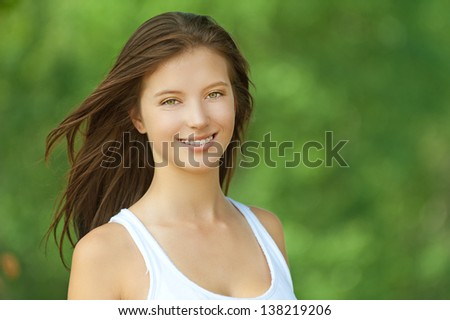 Portrait of smiling beautiful young woman close up, against background of summer green park. - stock photo