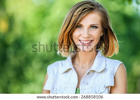 Portrait of smiling beautiful young woman close-up, against green of summer park.