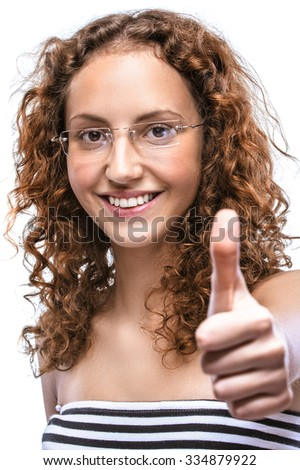 Portrait of smiling beautiful young woman in a striped vest with a raised thumb up, isolated on a white background. - stock photo