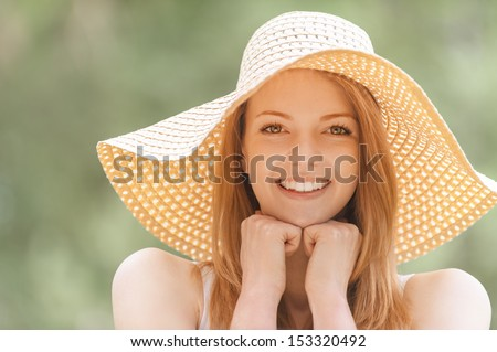 Portrait of smiling beautiful young woman in summer cap closeup, against green of summer park. - stock photo
