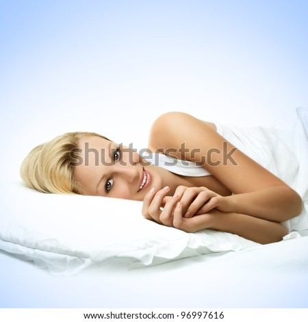 Portrait of smiling beautiful young woman relaxing in the bed. - stock photo