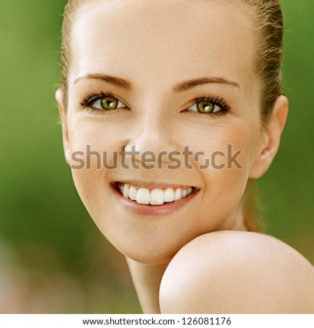 Portrait of smiling beautiful young woman with bare shoulders, against green of summer park.