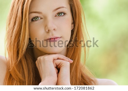 Portrait of smiling beautiful young woman with bare shoulders close up, against green of summer park. - stock photo