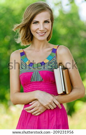 Portrait of smiling beautiful young woman with books, against green of summer park.