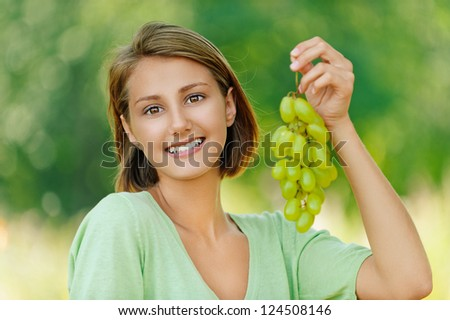 Portrait of smiling beautiful young woman with bunch of grapes, against background of summer green park. - stock photo
