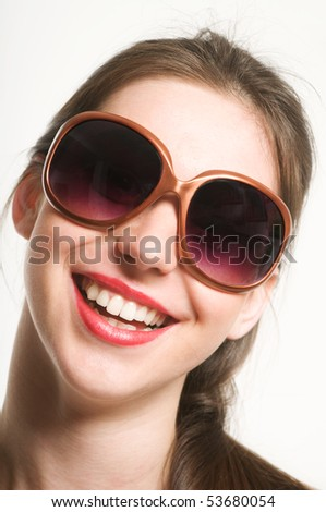 Portrait of smiling beautiful young woman with funy sunglasses - stock photo