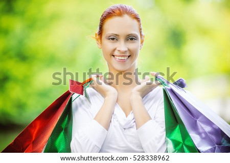 Portrait of smiling beautiful young woman with shopping, against green of summer park.