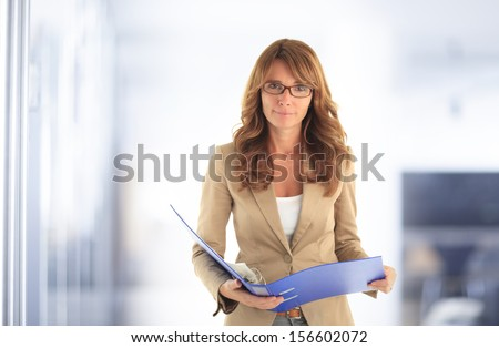 Portrait of smiling blond mature business woman standing in office. - stock photo