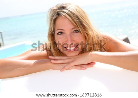 Portrait of smiling blond woman in deckchair