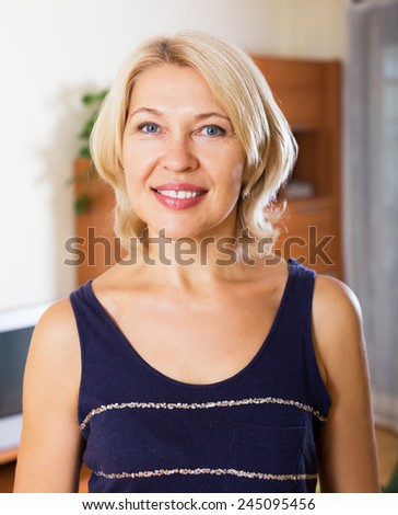 Portrait of smiling blond woman in home or office - stock photo