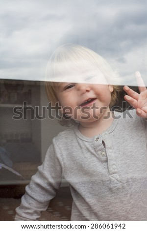 portrait of smiling blonde caucasian baby nineteen month age chubby face looking at camera through reflecting glass door - stock photo