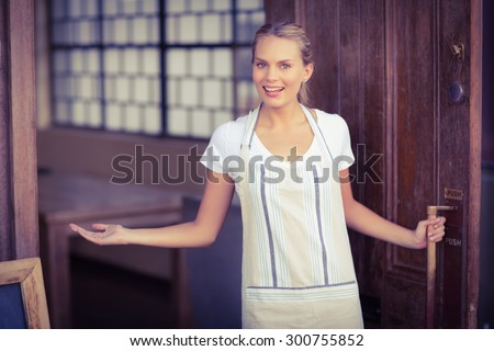 Portrait of smiling blonde waitress welcoming at coffee shop