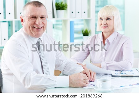 Portrait of smiling boss looking at camera at workplace with mature woman looking at him on background