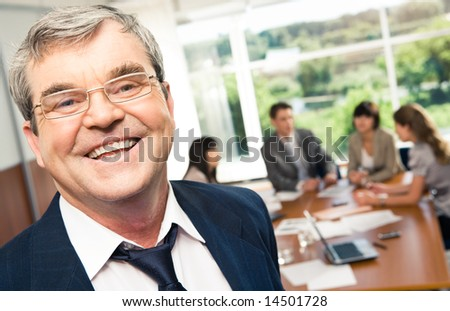 Portrait of smiling boss with glasses in a working environment