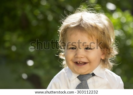 Portrait of smiling boy child with blonde curly hair and round cheeks in white shirt with necktie looking forward sunny day outdoor on natural green tree leaves background copyspace, horizontal photo - stock photo