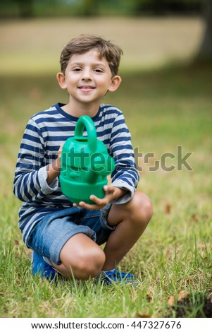Portrait of smiling boy holding a watering can in park