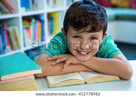 Portrait of smiling boy with book at table in school library - stock photo