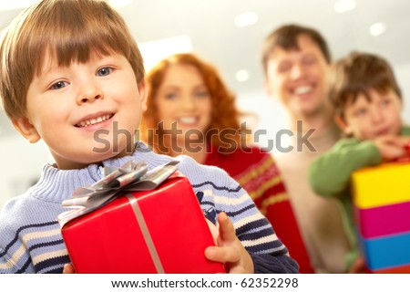 Portrait of smiling boy with gift looking at camera on background of family - stock photo