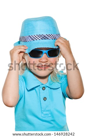 portrait of smiling boy with sun glasses in blue hat and shirt on white - stock photo