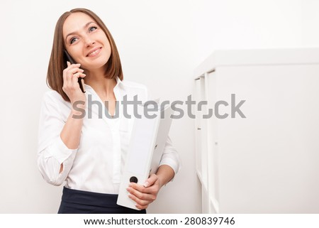 Portrait of smiling brunette businesswoman phoning while standing with a folder in office