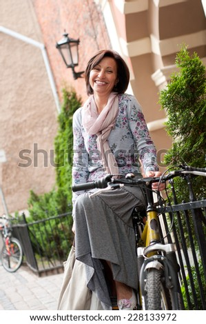 Portrait of smiling brunette middle aged woman in town  - stock photo