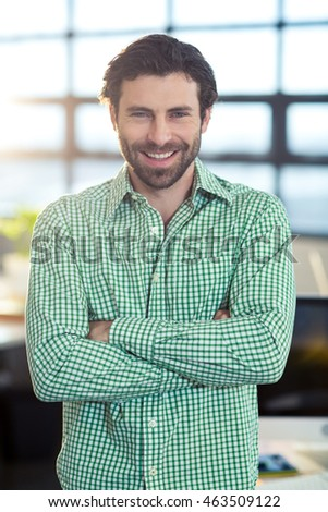 Portrait of smiling business executive standing with arms crossed in office