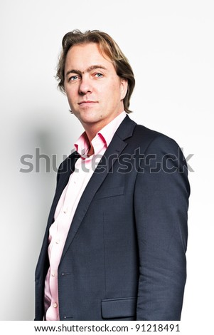 Portrait of smiling business man against white wall in office