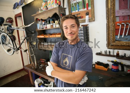 Portrait of smiling business owner in bicycle shop - stock photo