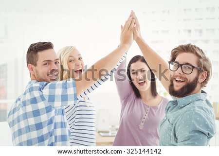 Portrait of smiling business people giving high five at office - stock photo
