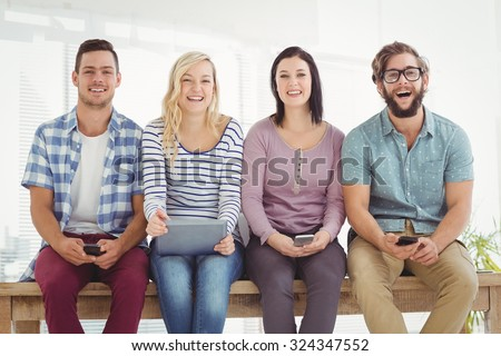 Portrait of smiling business people holding electronic gadgets while sitting on desk in office - stock photo