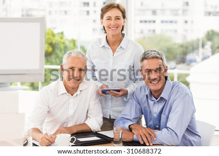 Portrait of smiling business people looking at camera in the office - stock photo