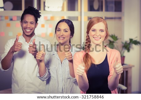 Portrait of smiling business people showing thumbs up in office - stock photo