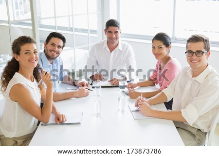 Portrait of smiling business people sitting at conference table in office - stock photo