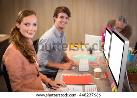 Portrait of smiling business people sitting in office - stock photo