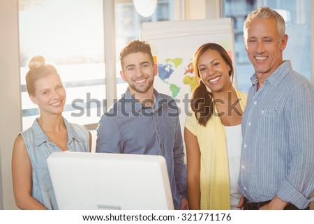 Portrait of smiling business people using computer in meeting room at creative office - stock photo