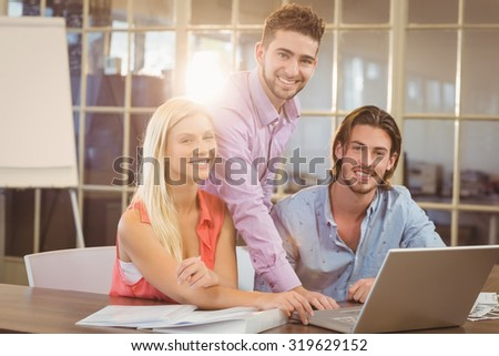 Portrait of smiling business people working in creative office - stock photo