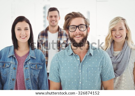 Portrait of smiling business professionals standing in office - stock photo