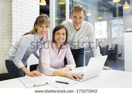 Portrait of smiling Business team in modern office, looking camera - stock photo