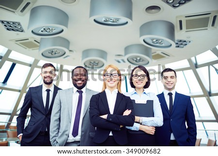 Portrait of smiling business team standing at office - stock photo