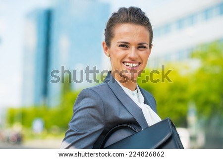 Portrait of smiling business woman with briefcase in office district