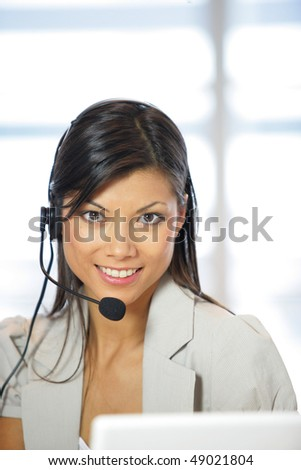 Portrait of smiling business woman with headset - stock photo