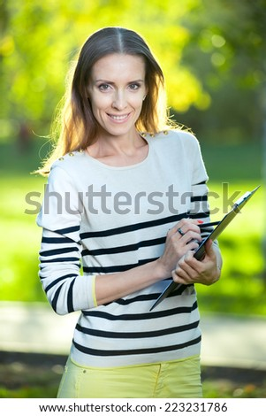 Portrait of smiling business woman with paper folder and pad, against green city park background. Student. - stock photo