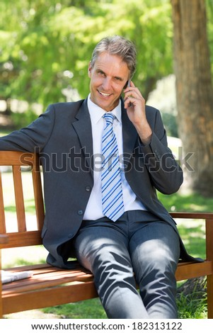 Portrait of smiling businessman answering smart phone while sitting on park bench