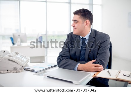 Portrait of smiling businessman at his workplace