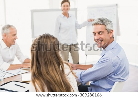 Portrait of smiling businessman during a presentation in the office - stock photo