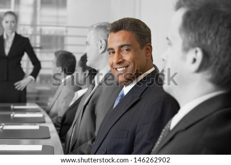 Portrait of smiling businessman in conference room with colleagues - stock photo