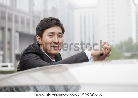 Portrait Of Smiling Businessman Leaning On Car - stock photo