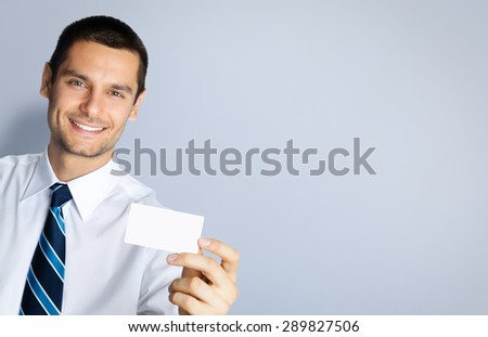 Portrait of smiling businessman showing blank business or plastic credit card, against grey background. Copyspace blank area for slogan or text. Business and success concept. - stock photo