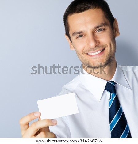 Portrait of smiling businessman showing blank business or plastic credit card, with copyspace area for slogan or text message, posing at studio, against grey background - stock photo