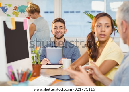 Portrait of smiling businessman using digital PC surrounded with colleagues in creative office - stock photo